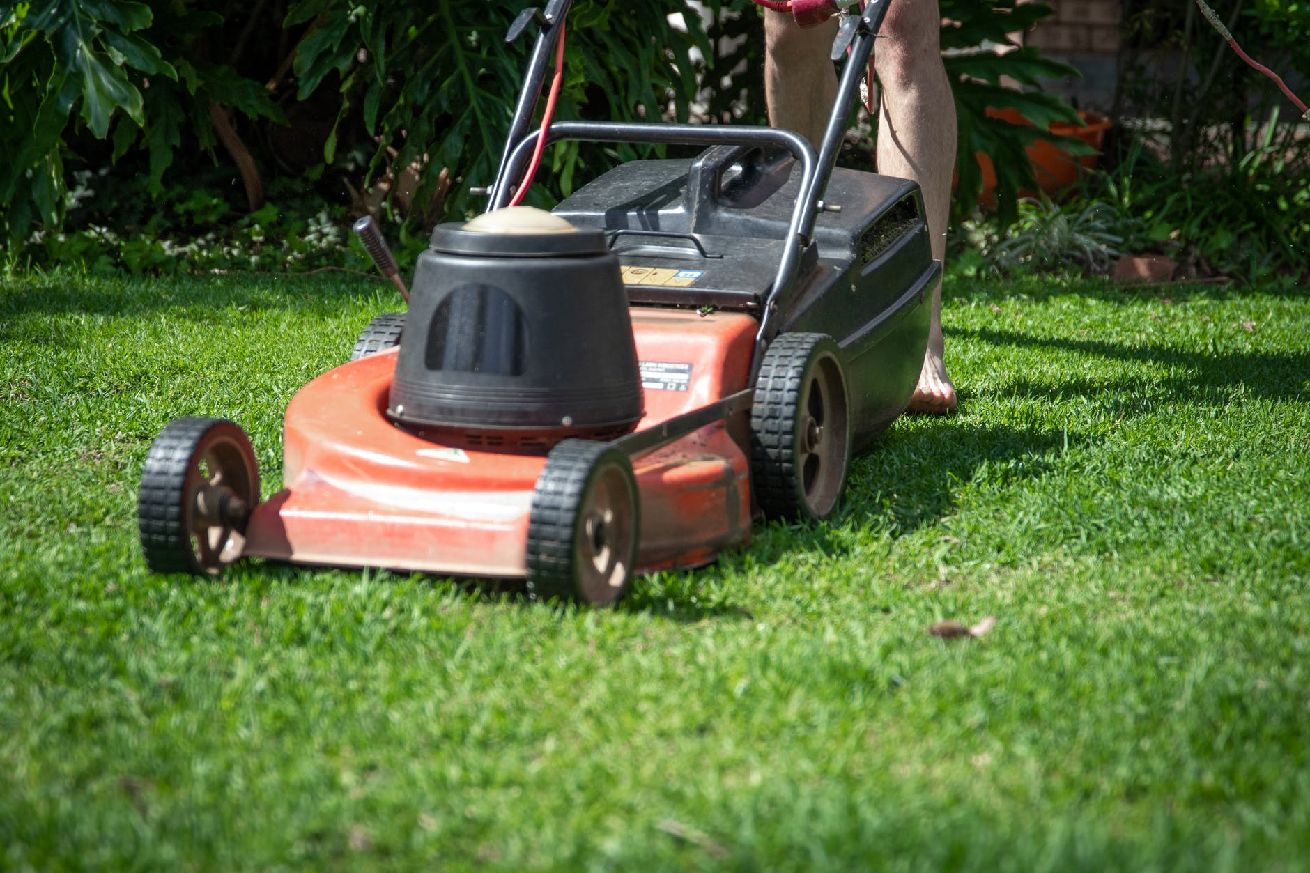 barefoot person mowing lawn