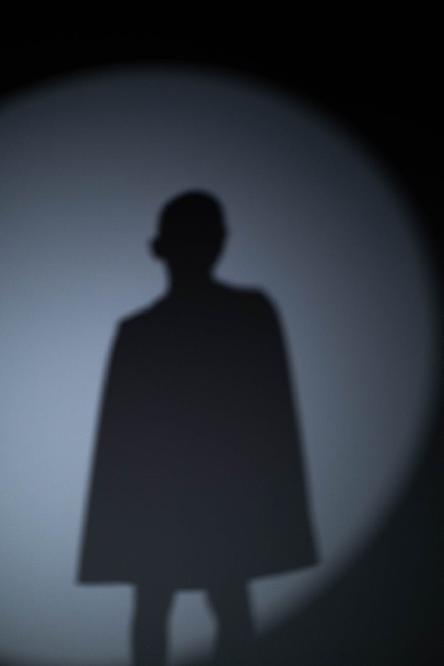 shadow of young male child wearing a cape