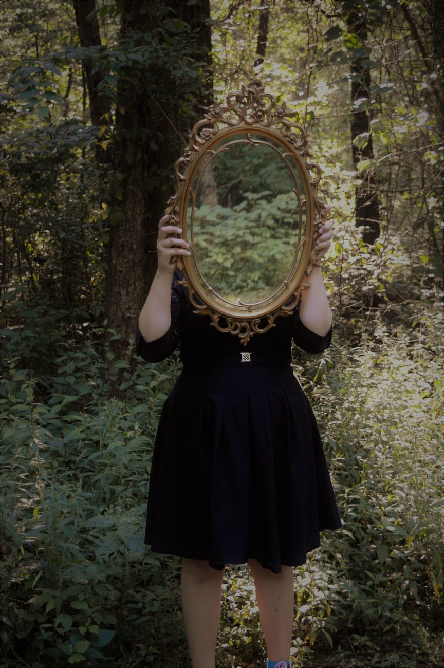 girl holding mirror over face in forest