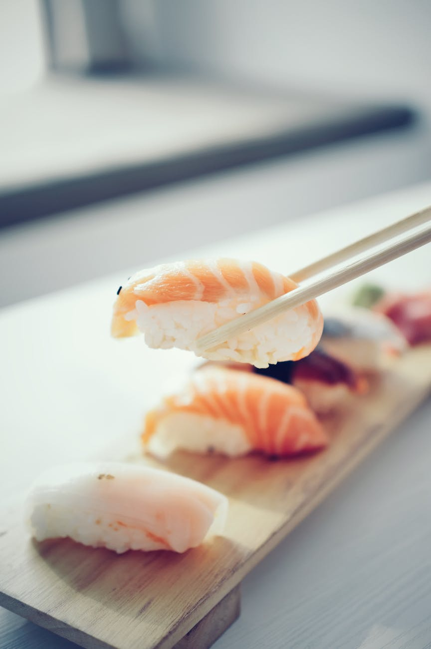 nigiri on wooden plank with chopsticks