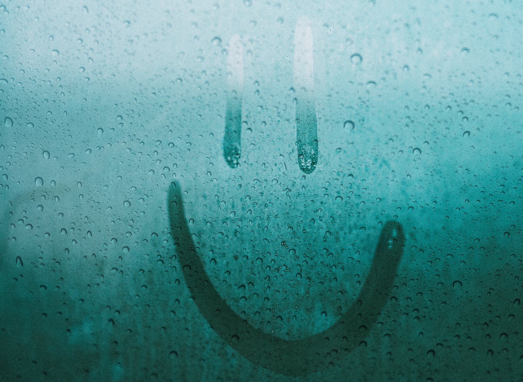 smile drawn with finger in condensation