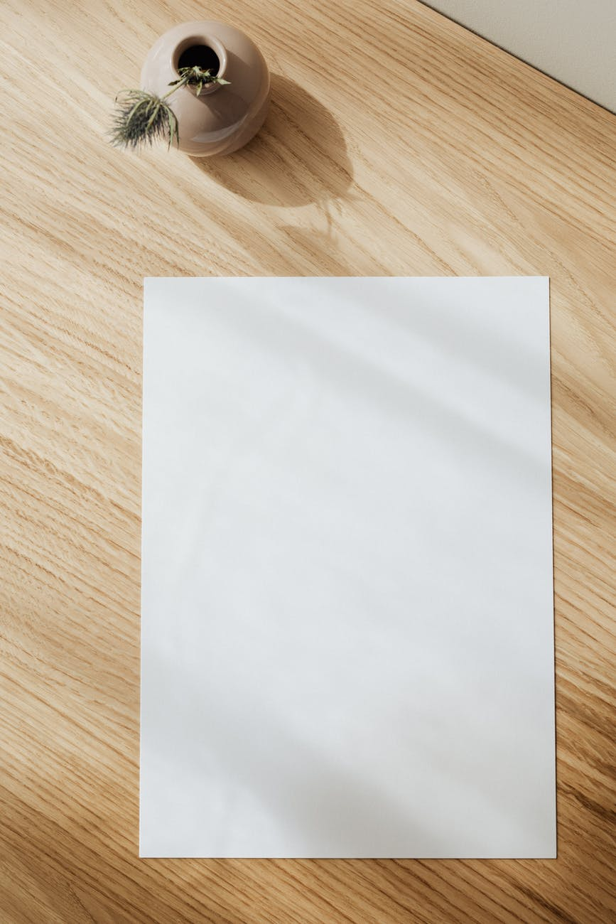 blank sheet of paper on desk with quill
