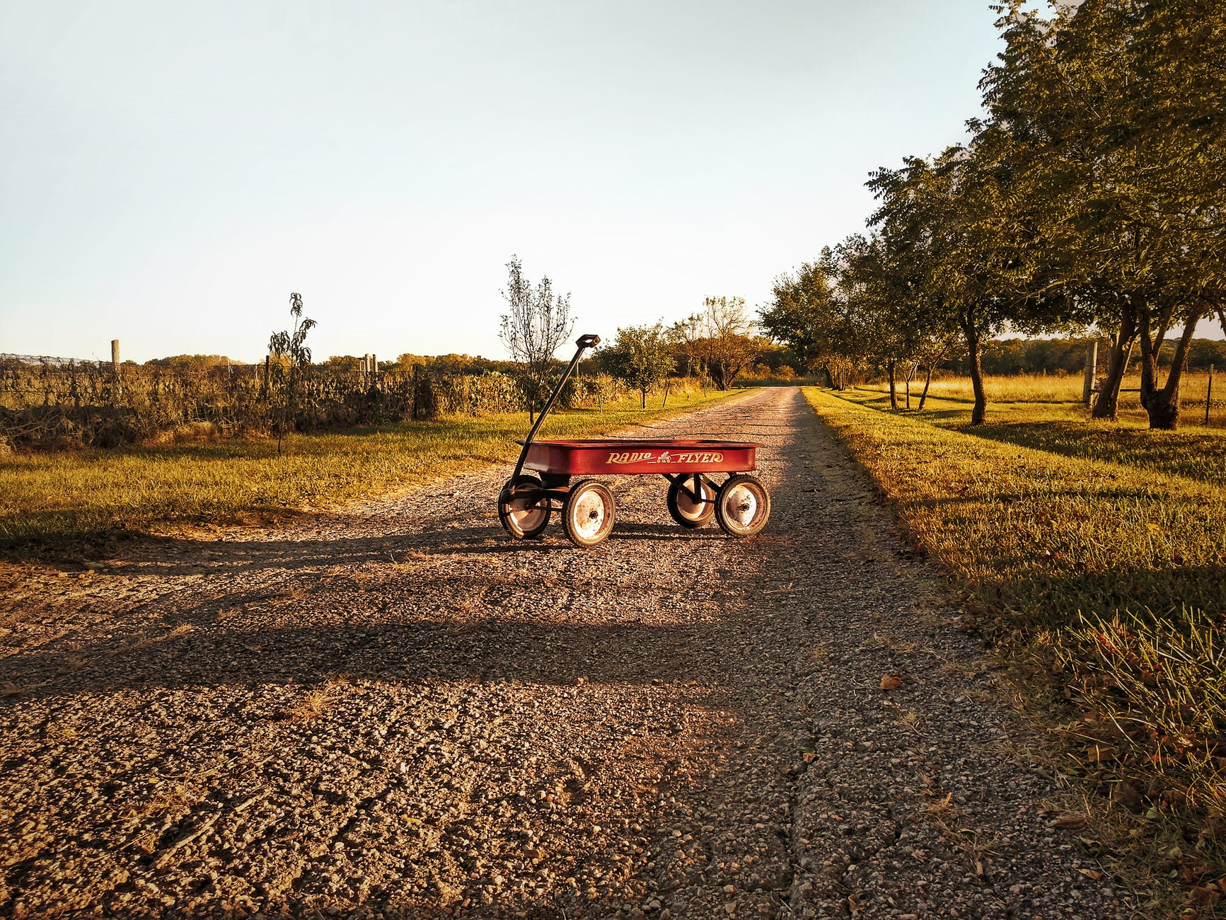 radio flyer wagon on gravel road with grass on each side with clear blue sky