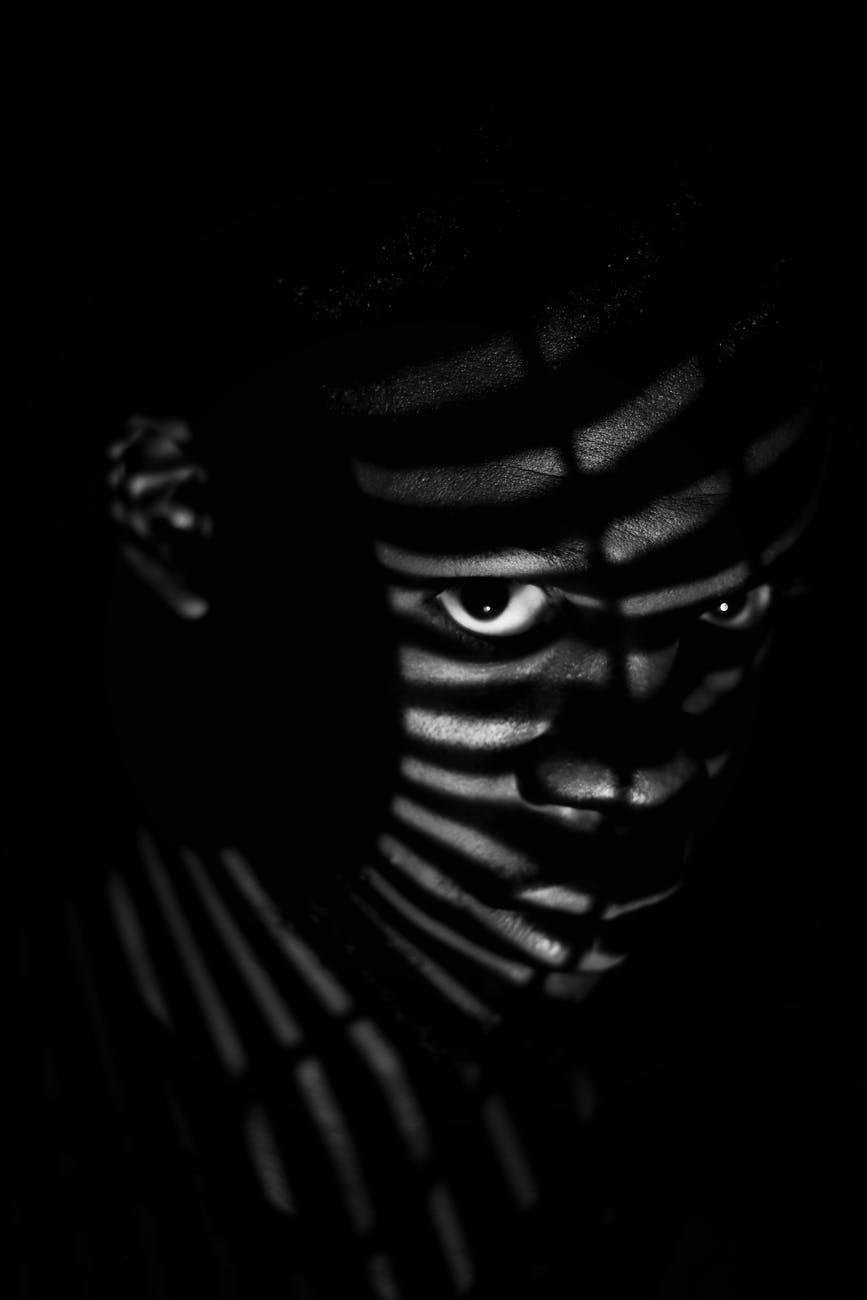 man in shadow with slats of light on his face