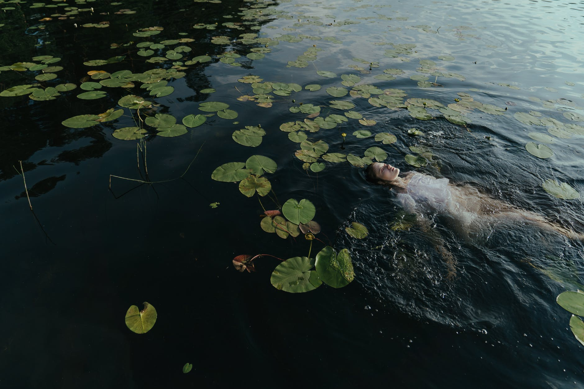 woman floating on her back in water with lily pads