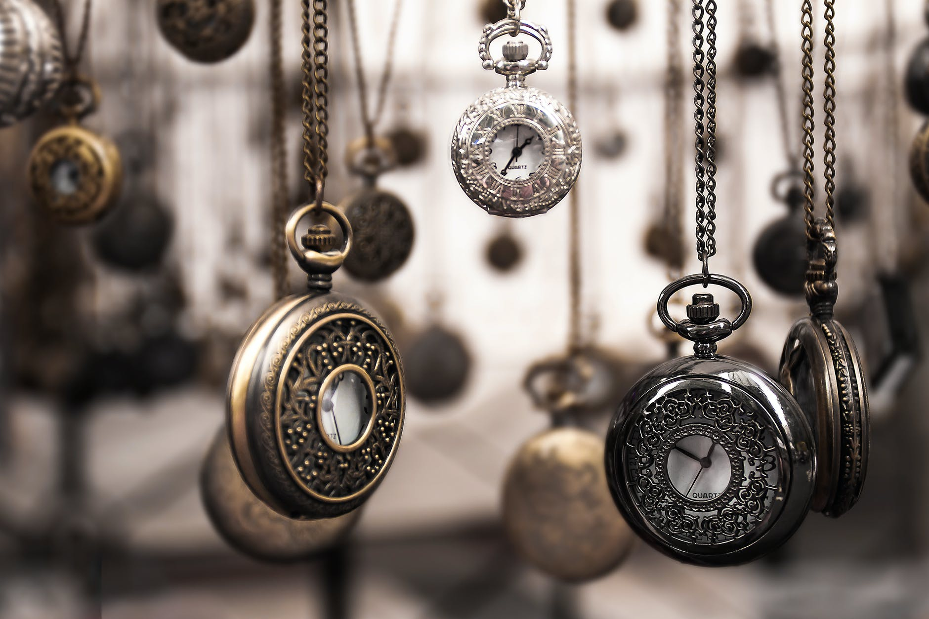 pocket watches hanging in front of a light background