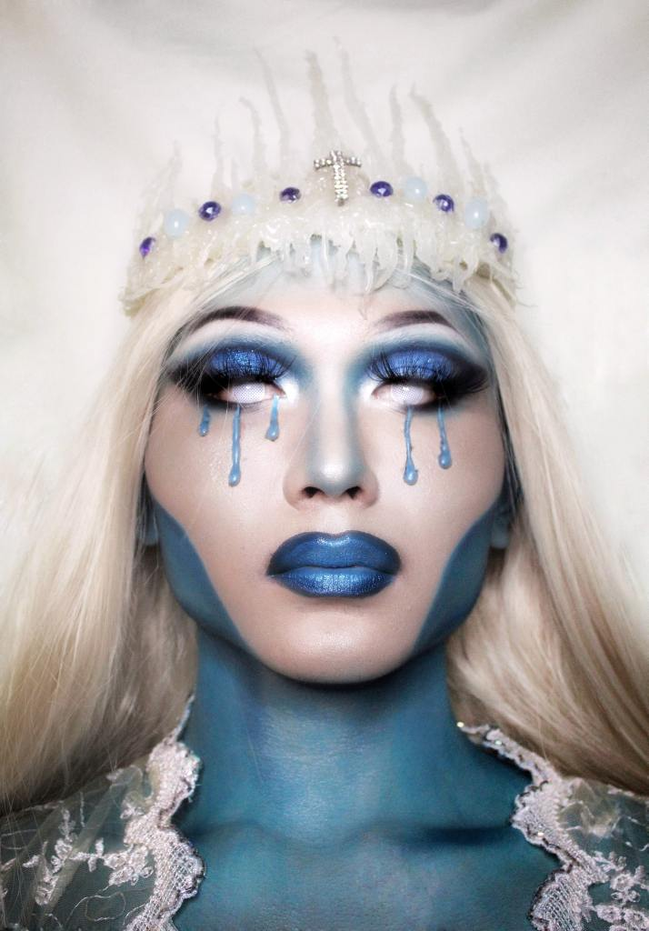 Woman with white hair and blue make-up and blue tears against white background