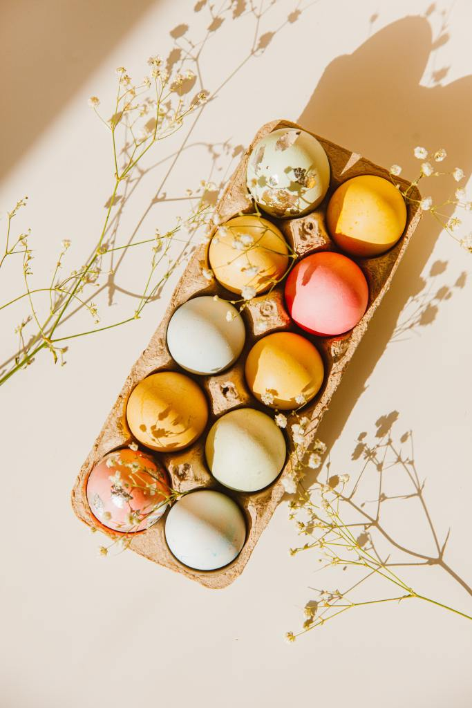 multi colored eggs in carton with baby's breath flowers
